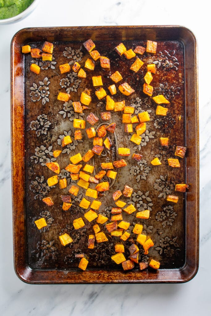 Roasted butternut squash on a weathered baking sheet