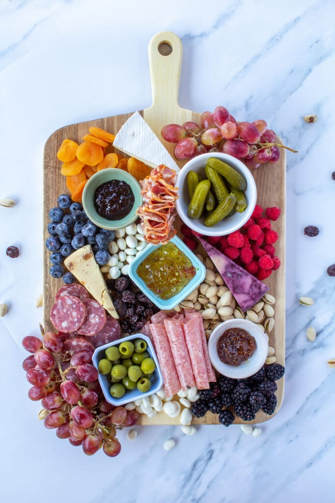 a wooden board filled with fruits, crackers, meats, and other ingredients