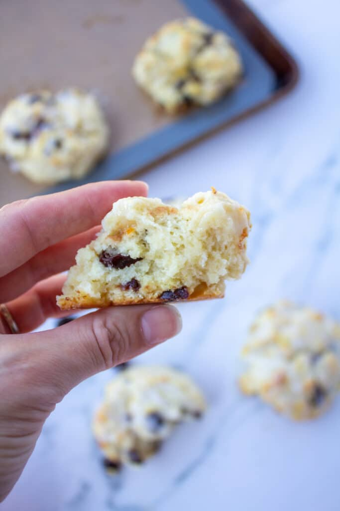 a scone with a bite taken out held in the air by a hand