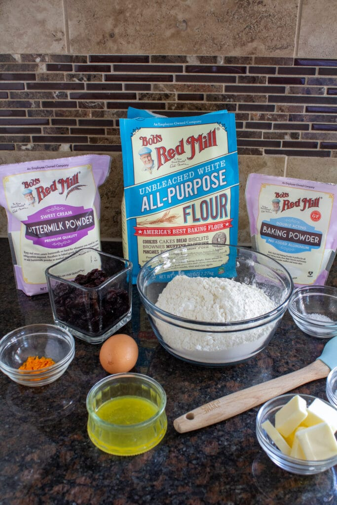 Bob's Red Mill flour, baking powder, and buttermilk powder on a counter with ingredients for cherry scones