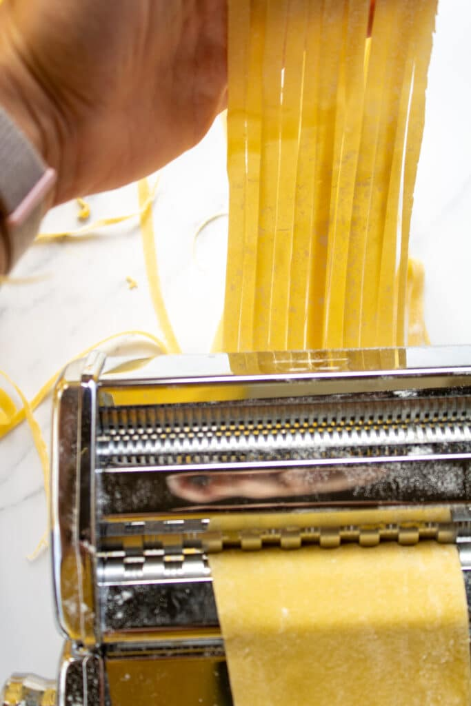 cut pasta going through a pasta machine