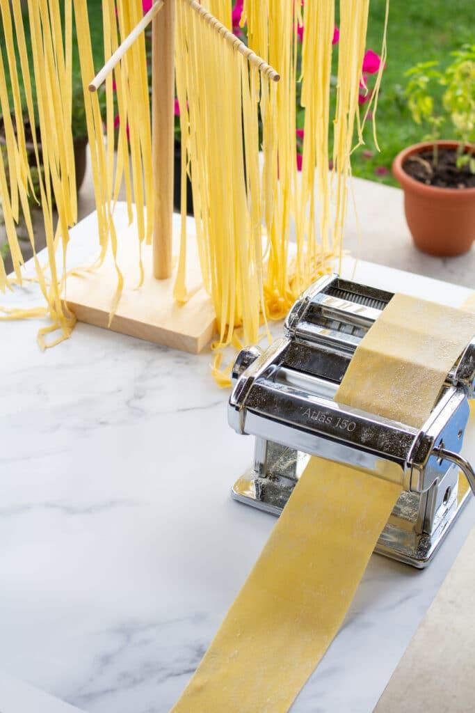 a piece of dough in a pasta machine next to a rack of cut pasta