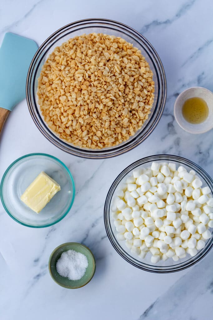 Rice cripies, marshmallows, butter, salt, and vanilla in bowls on a white marble surface