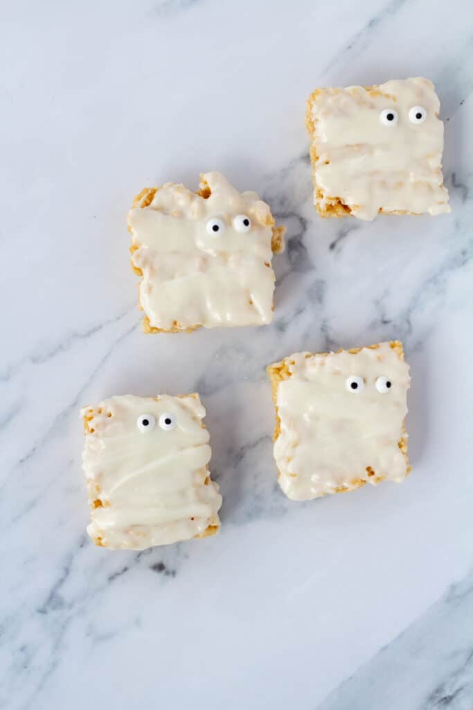 Four mummy rice crispy treats covered with icing with googly eyes on a white marble counter