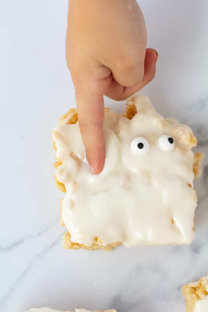 A child's finger in the icing of a mummy rice crispy treat