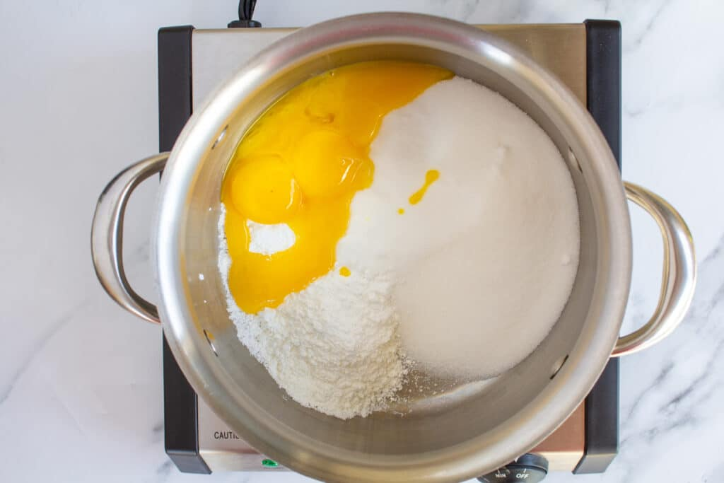 a pot with eggs, sugar, and cornstarch