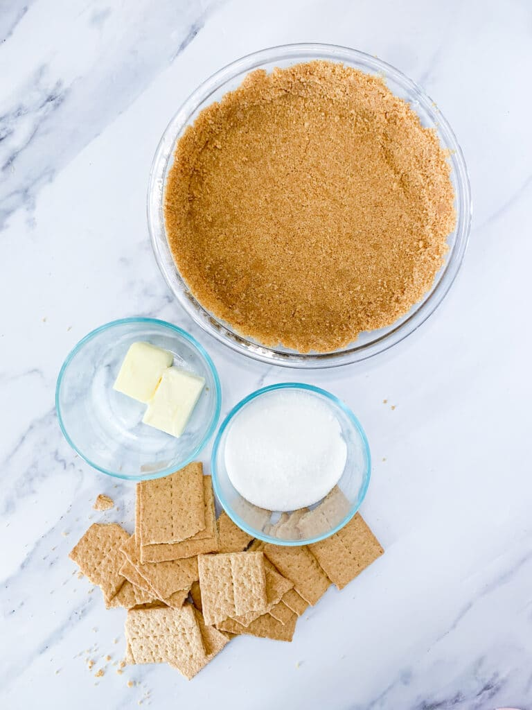 graham cracker crust ingredients sitting on a white marble background