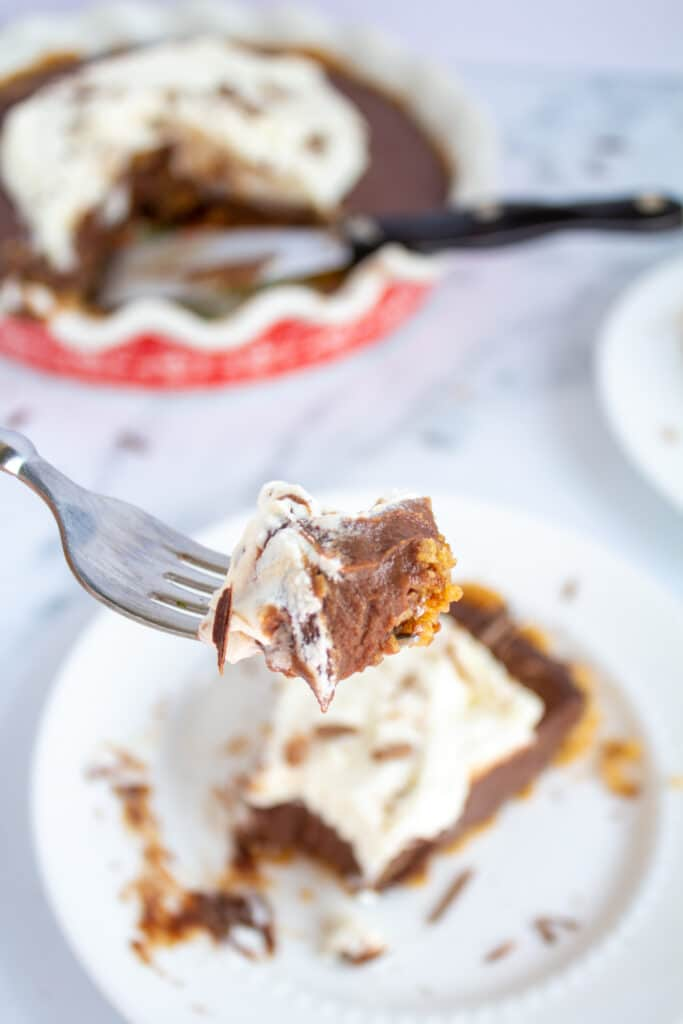 a close up of a fork with a piece of chocolate pie and whipped cream with the slice and pie in the background