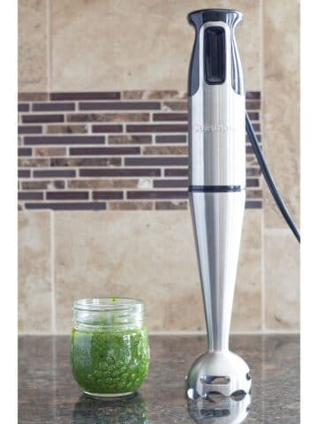 an immersion blender standing on a counter and sitting next to pesto