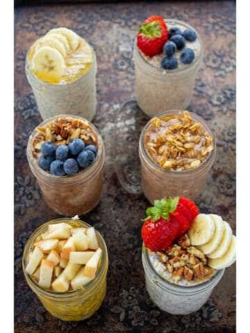 an overhead view of 6 jars of oats with toppings