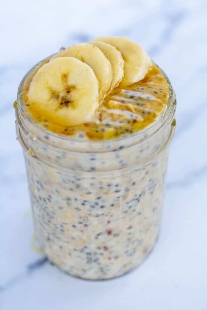 straight on view of oats in a jar topped with bananas and honey