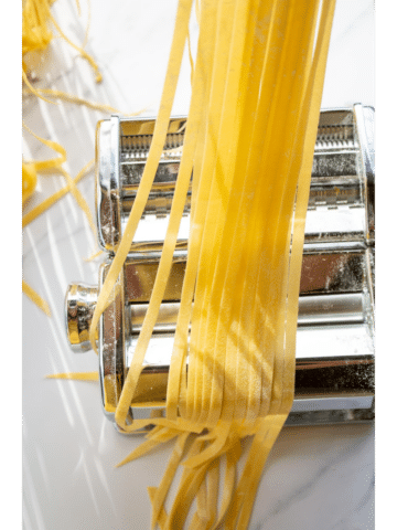 strands of pasta held over a pasta machine