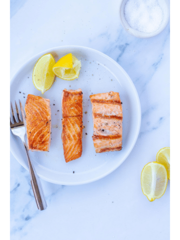 Three pieces of salmon on a white plate next to lemons