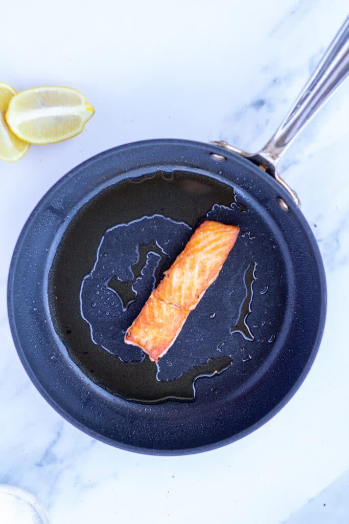 One piece of salmon in a saute pan