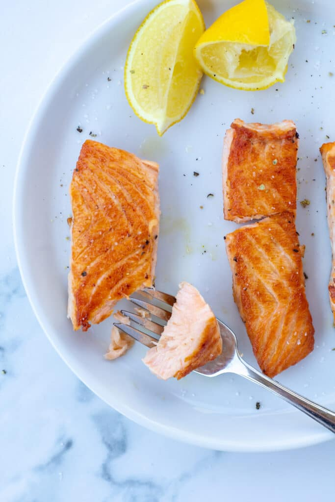 Three pieces of salmon on a white plate with a bite taken out of one