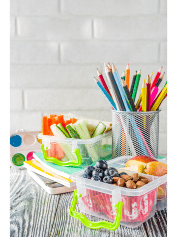 a lunch box with food on a wood surface with a cup of colored pencils sitting next to it