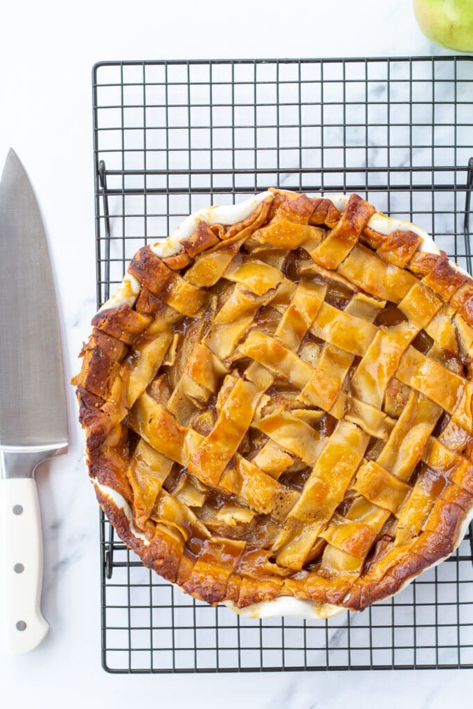 A whole apple pie sitting on a cooling rack next to a knife
