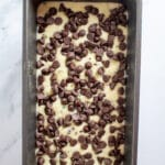 Bread batter in a loaf pan with chocolate chips on top