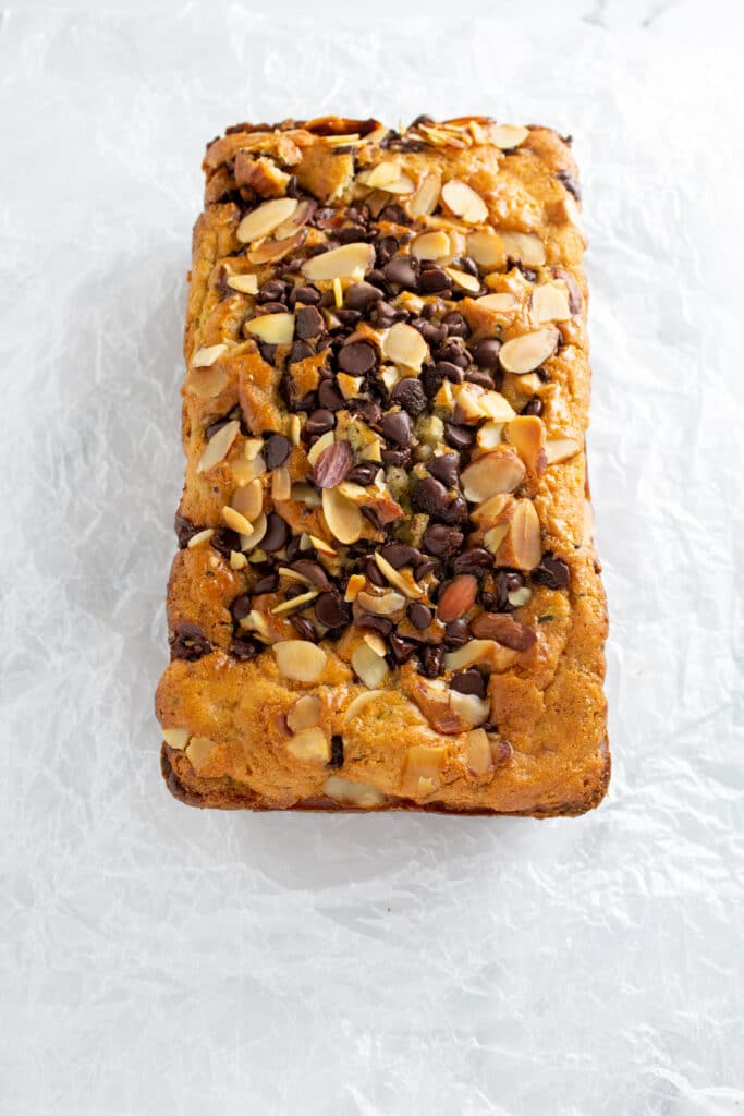 A whole loaf of bread with chocolate chips and sliced almonds on a white background