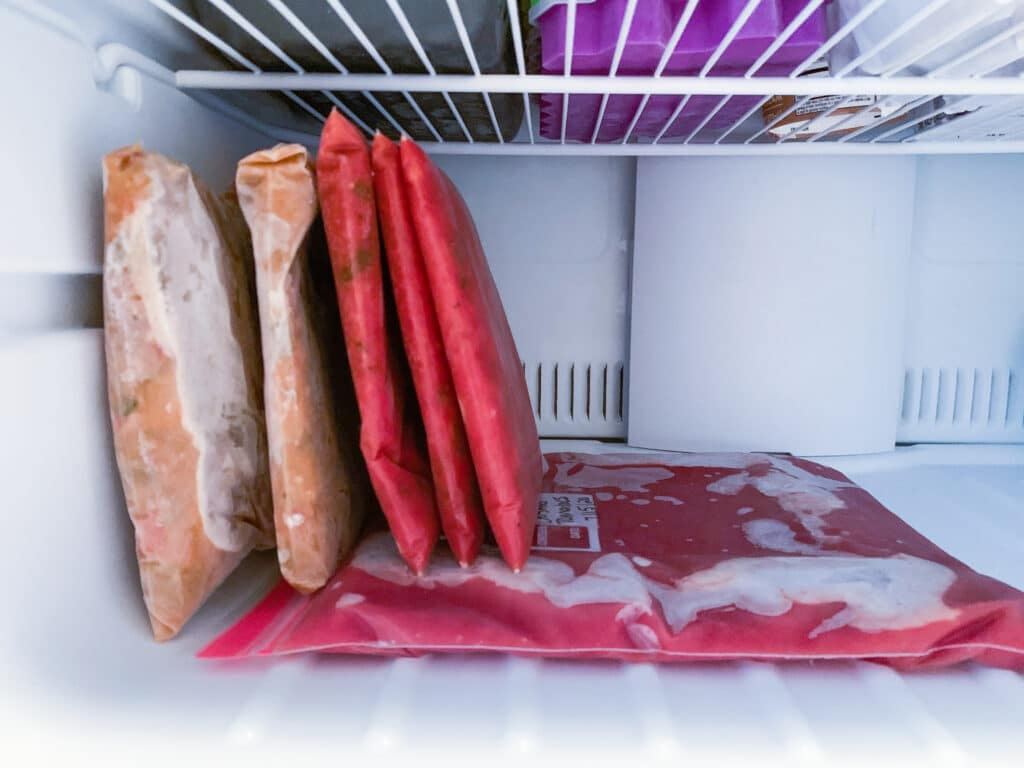 Bags filled with food frozen flat and now standing up in a freezer.