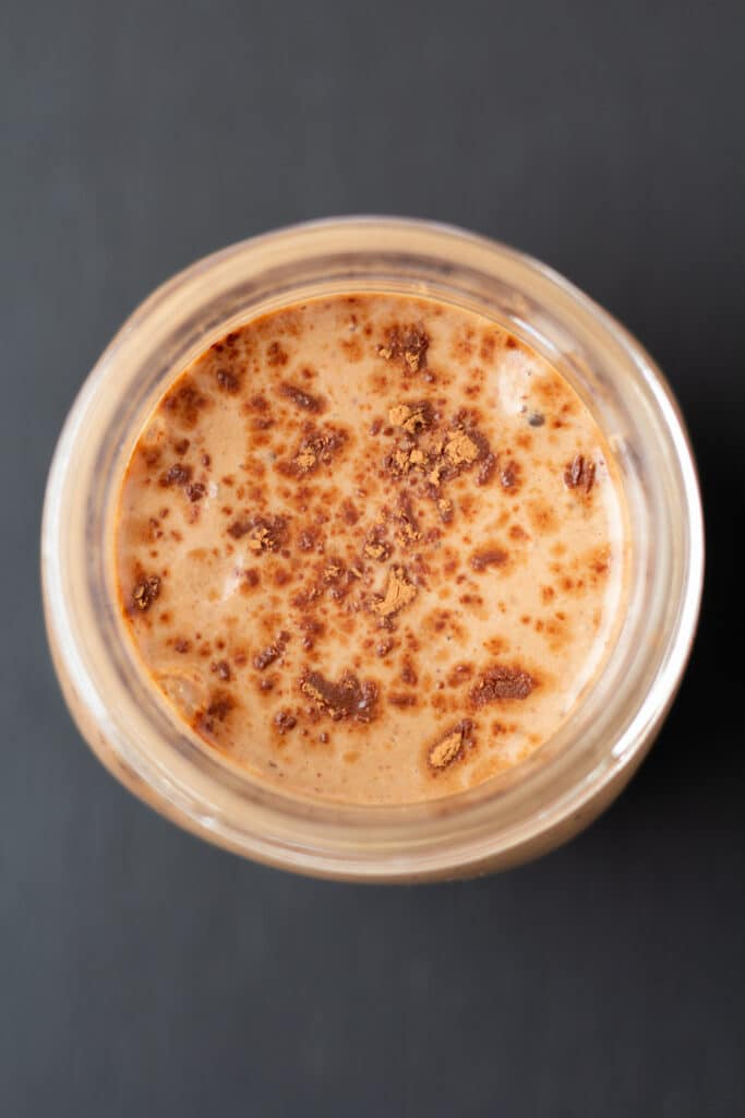 overhead view of a chocolate smoothie with cocoa powder on top