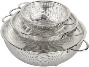 A set of three stainless steel colanders nested together
