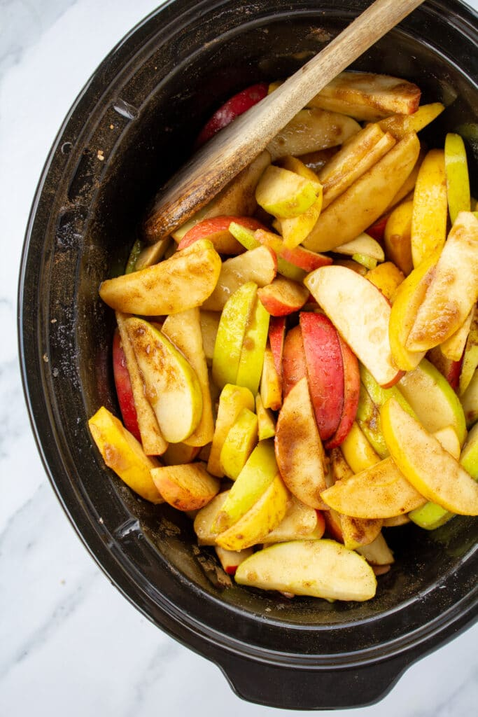 crockpot-full-of-coated-apples-and-a-wooden-spoon-sitting-on-a-marble-counter