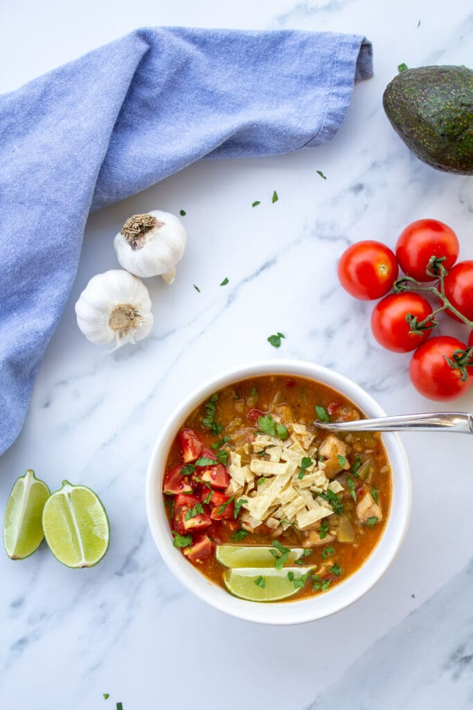 green chile in a bowl on a marble surface with tomatoes, garlic, limes, and avocado surrounding it