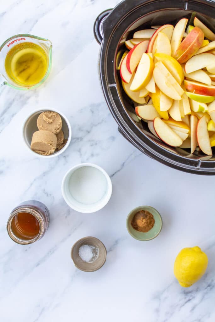 ingredients-for-apple-butter-next-to-a-slow-cooker-filled-with-sliced-apples