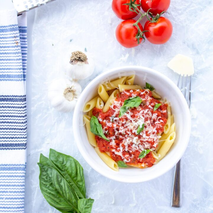 marinara sauce in a white bowl surrounded by garlic, basil leaves, tomatoes on the vine, a fork, and a white and blue napkin