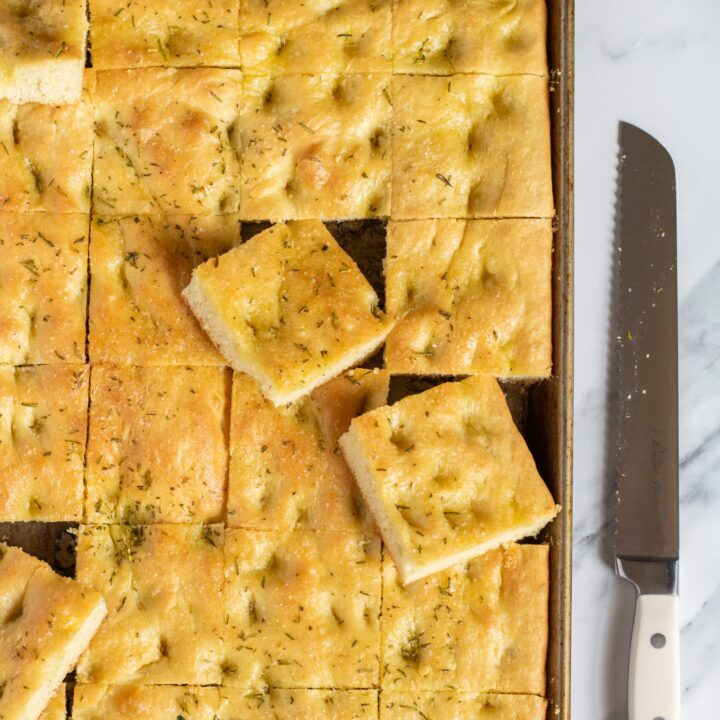 sliced focaccia bread in a sheet pan on a marble table with a long serrated knife next to the pan