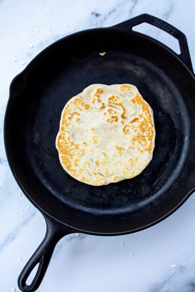 cooked tortilla in cast iron skillet